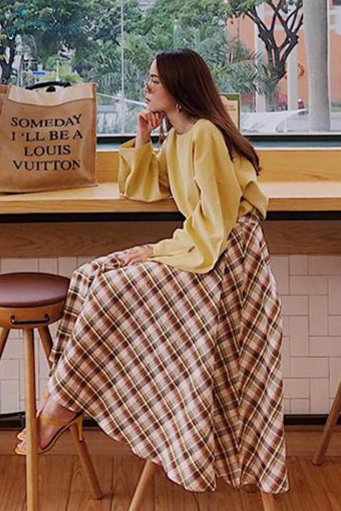 Theo phong cách cổ điển,chân váy xòe được Yến Trang phối cùng áo blouse tông vàng mơ nhẹ nhàng. Phụ kiện đi kèm là sandal quai mảnh và túi tote trên chất liệu vải bố.