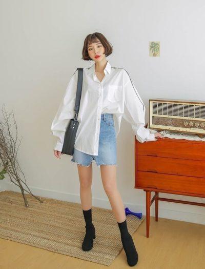 Phối cùng với váy jean đắp chéo làm nổi bật hơn kiểu áo sơ mi oversize