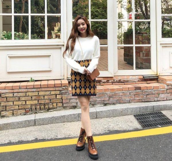 Áo trắng tay dài và chân váy họa tiết cùng boot màu da bò lại mang chút điệu đà