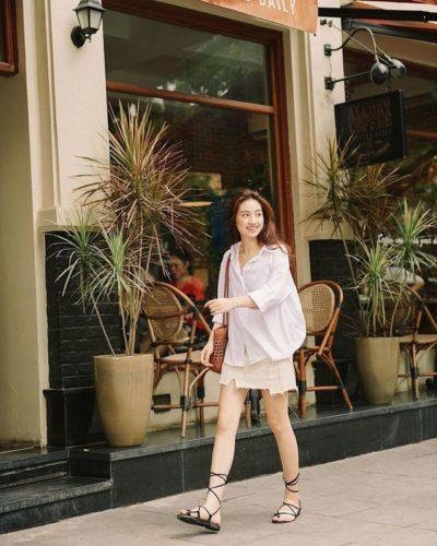 Áo sơ mi trắng form rộng và chân váy mà kem đi cùng sandal dây dạo phố tươi tắn