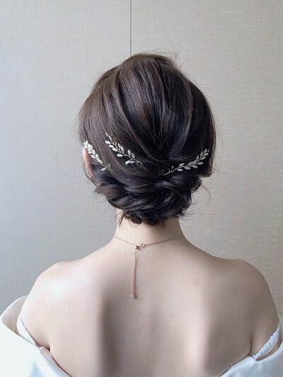 Đơn giản và yêu kiều là những gì mẫu tóc này đem lại cho cô dâu. Chỉ cần tết tóc hai bên và khéo léo ghim sau gáy kết hợp phụ kiện đơn giản là nàng đã tỏa sáng.
