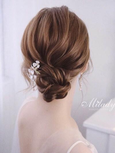 Tóc búi thấp gài hoa nhí như thế này giúp cô dâu hóa nàng tiểu thư cổ điển với vẻ đẹp sang trọng